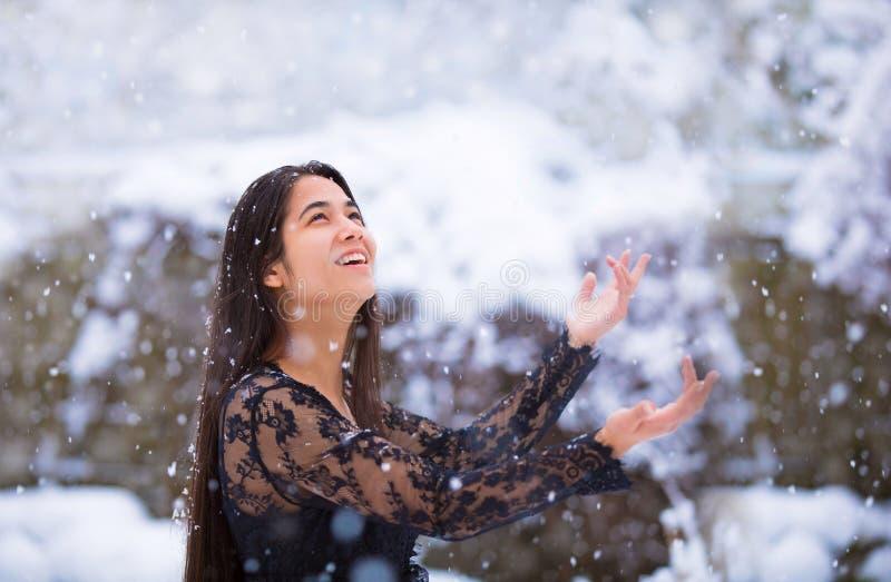 青少年的女孩捉住的雪花户外在冬天 免版税库存图片