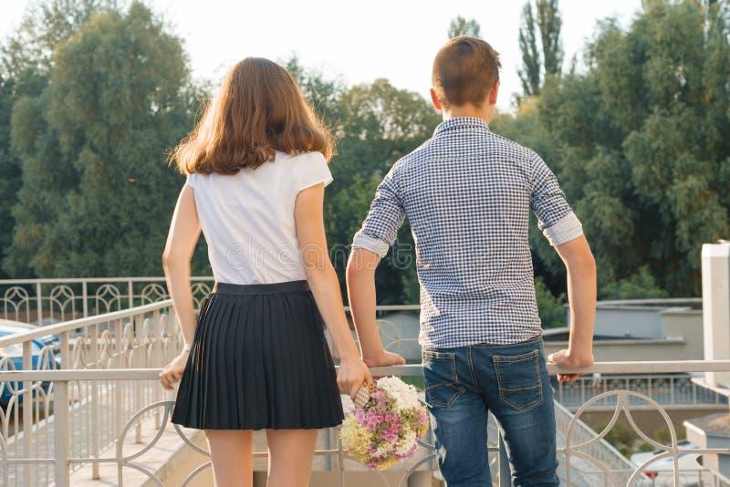 青少年的青年在手中站立夫妇男孩和的女孩,夏天好日子,女孩藏品花束 免版税库存照片
