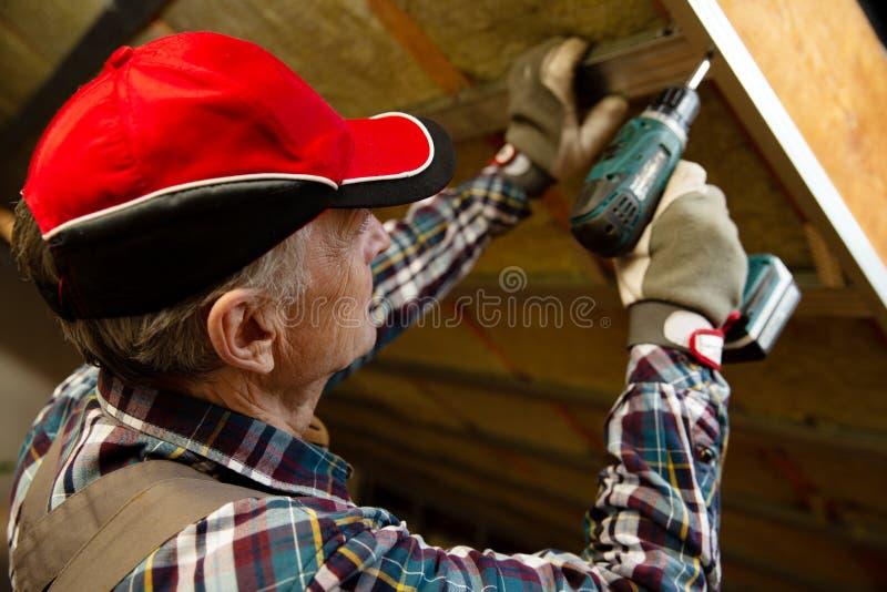 顶楼绝缘材料和整修 使用一把电螺丝刀的人固定的金属框架在用矿毛绝缘纤维报道的天花板 免版税库存图片