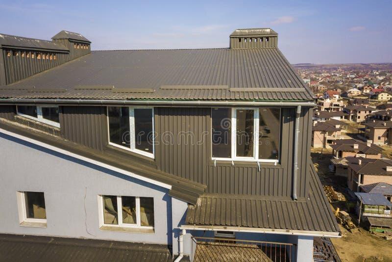 顶楼附录与塑料窗口、用棕色金属装饰支持的板条盖的屋顶和墙壁的室外部鸟瞰图, 免版税库存图片