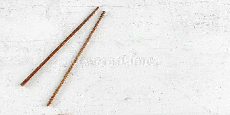 顶面下来视图-对在白板的黑暗的木筷子 能使用作为横幅为亚洲人/中国菜,文本的空间  免版税库存照片