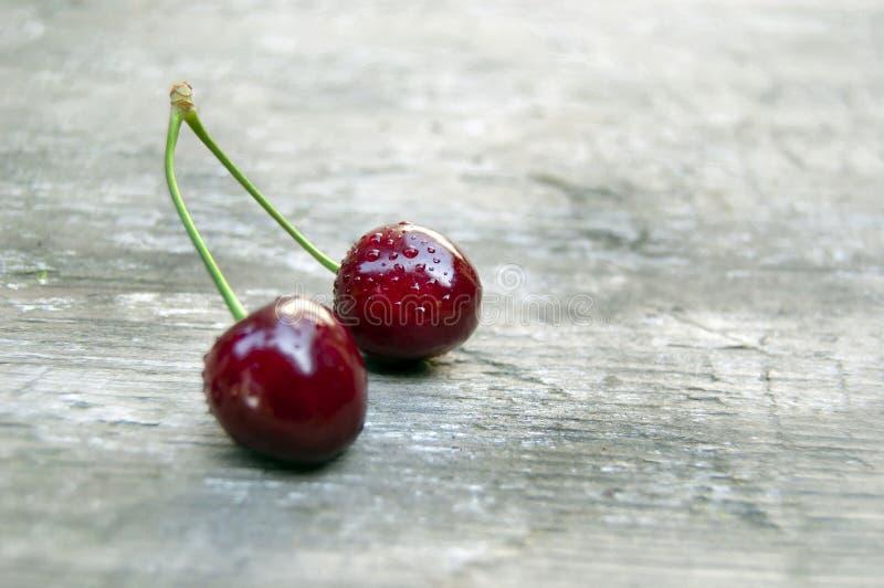 顶面射击,关闭与水下落的新鲜的甜樱桃在轻的土气木桌背景,选择聚焦,空间为 库存照片