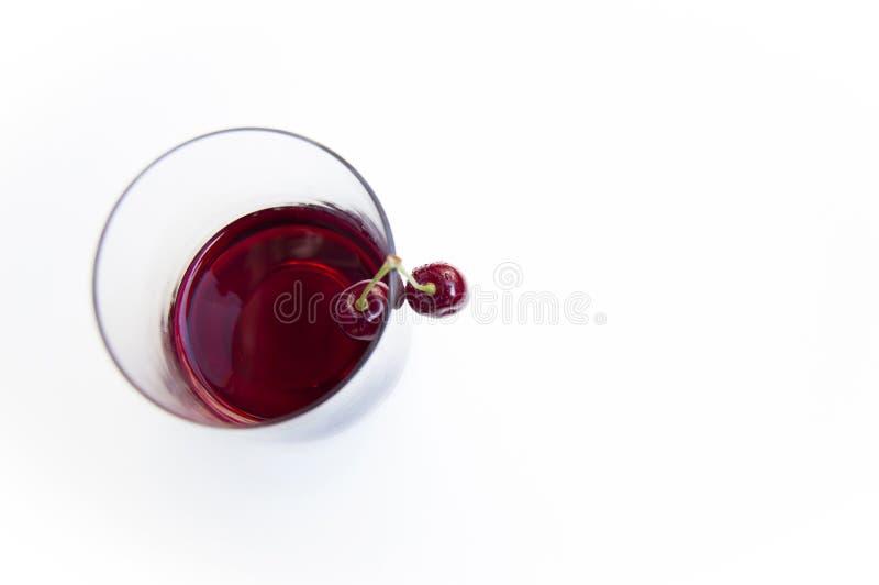 顶面射击,关闭与水下落的新鲜的甜樱桃,在白色背景隔绝的玻璃的樱桃汁,选择聚焦, 免版税库存图片