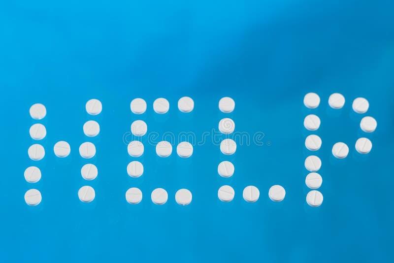 题字帮助被计划在蓝色背景的白色片剂 库存照片