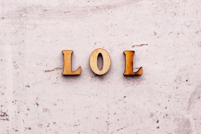 题字笑在木信件的大声的简称之外的洛勒在轻的背景 免版税图库摄影