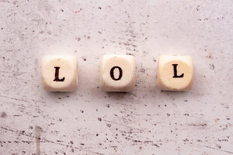 题字笑在木信件的大声的简称之外的洛勒在轻的背景 免版税库存照片