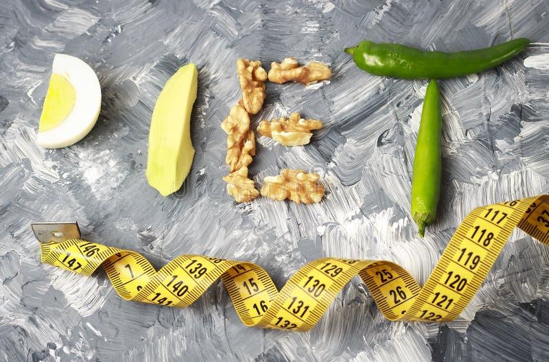 题字饮食由坚果、鸡蛋和鲕梨制成 在重量白人妇女的美好的腹部概念损失 库存照片