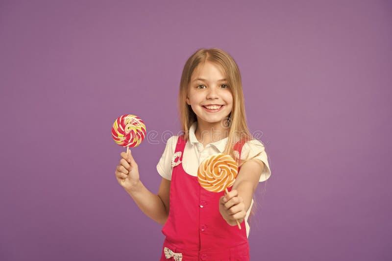 食物和点心 与棒棒糖的女孩微笑在紫罗兰色背景 愉快的孩子用在紫色背景的漩涡焦糖 免版税库存图片