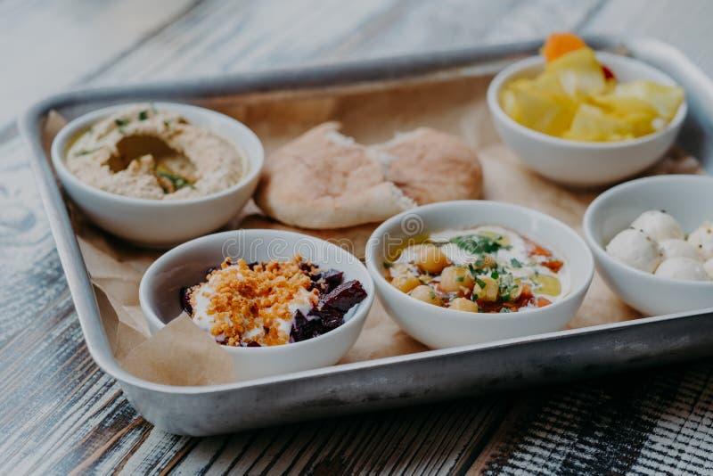食物和营养概念 晚餐的传统以色列盘 可口hummus,甜菜用香料,核心的蕃茄,皮塔饼盘子  免版税库存图片