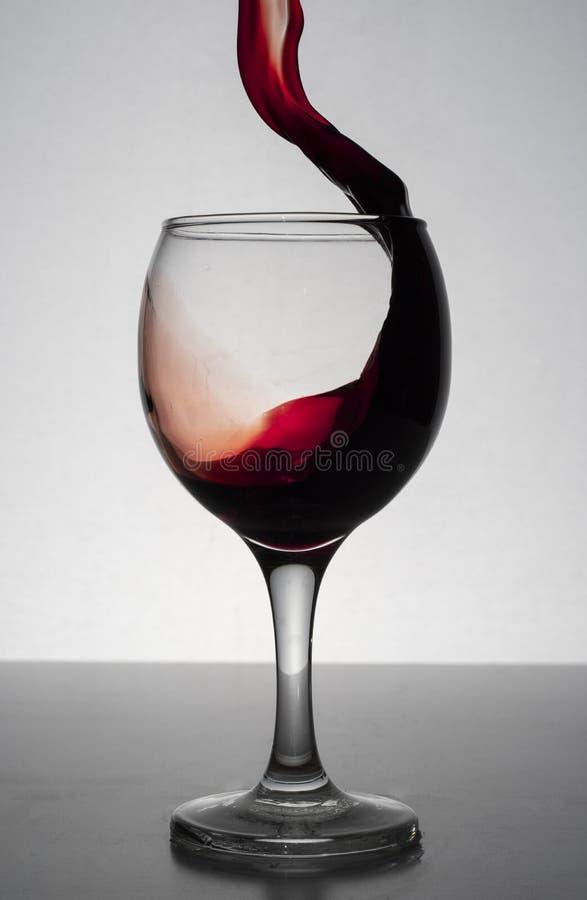 飞溅在葡萄酒杯外面的红葡萄酒 库存图片