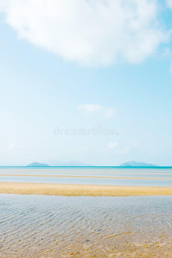 风景热带海在夏天 放松在金黄沙滩、白色云彩和浅兰的天空,海岛背景的波痕 库存图片
