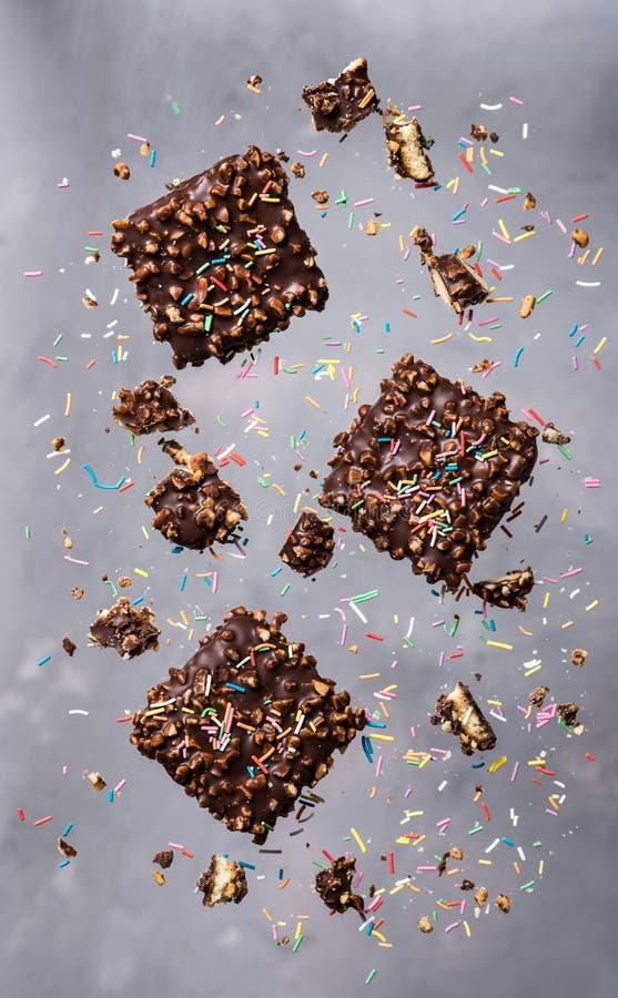 飞行的曲奇饼 与坚果和糖的巧克力片洒落在行动的小点 图库摄影