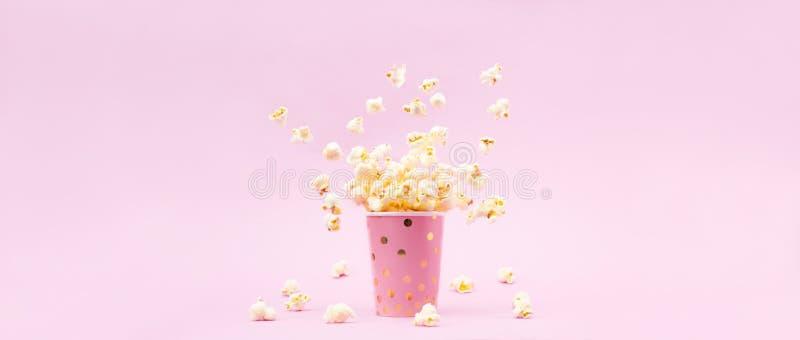 飞行的玉米花在一块明亮的玻璃和在桃红色背景 图库摄影