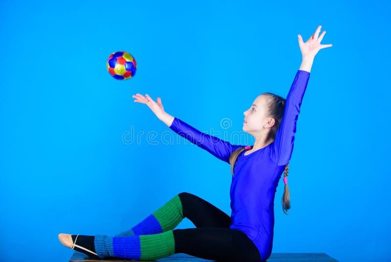 飞行 体操 有球的愉快的儿童运动员 体育和健康 健身饮食 能量 杂技健身房锻炼 免版税库存照片