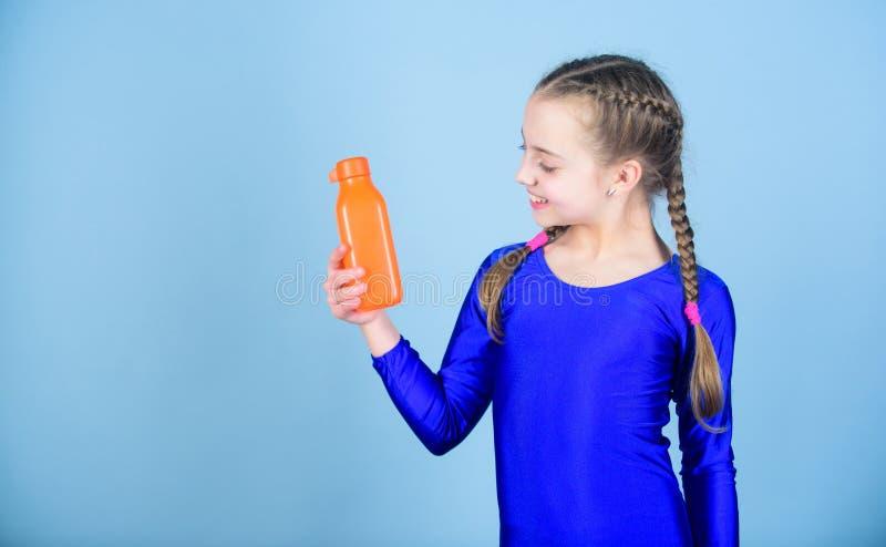 饮料的孩子逗人喜爱的女孩体操运动员体育紧身连衣裤举行瓶 水分平衡和坚硬健身房训练 喝更多水 保留 免版税库存照片