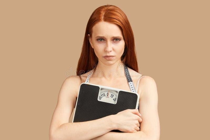 饮食和重量,年轻女人在手上的拿着标度感到哀伤和沮丧 免版税库存照片