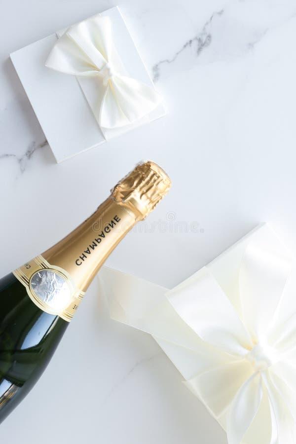 香槟瓶和一个礼物盒在大理石 免版税库存图片