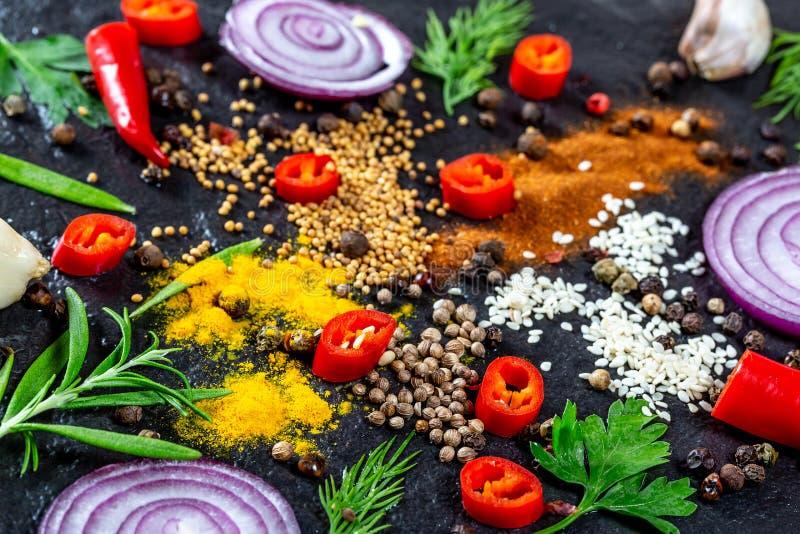 香料不同形式和草本、辣椒、大蒜和葱在黑石背景 免版税库存照片