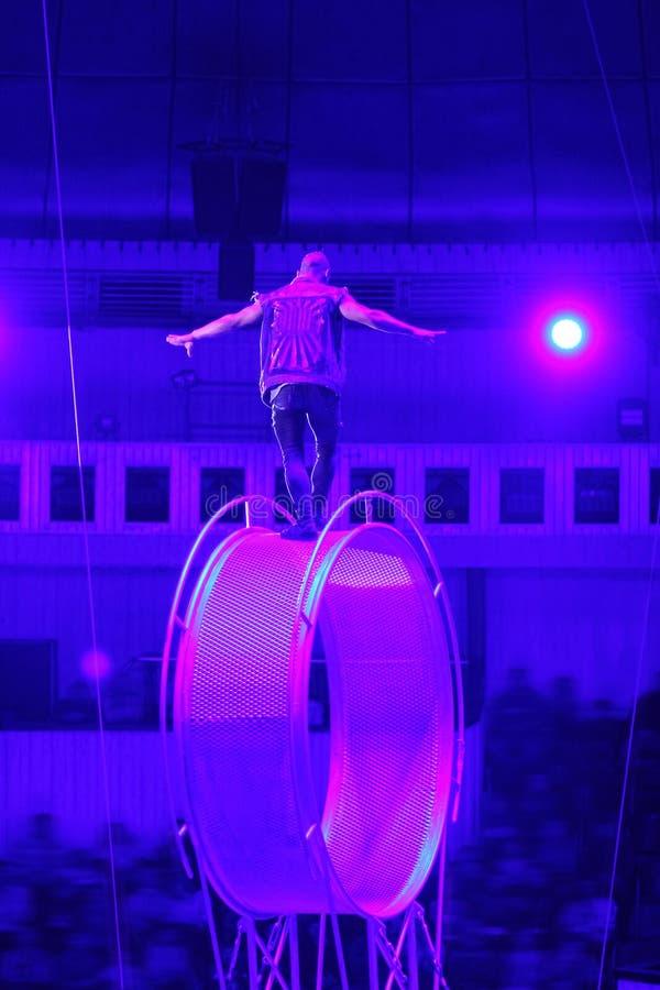 马戏团演员/杂技演员在死亡/空间轮子顶部手纺车  危险工作 免版税库存照片