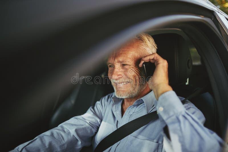 驾驶他的汽车的微笑的老人谈话在手机 免版税库存照片