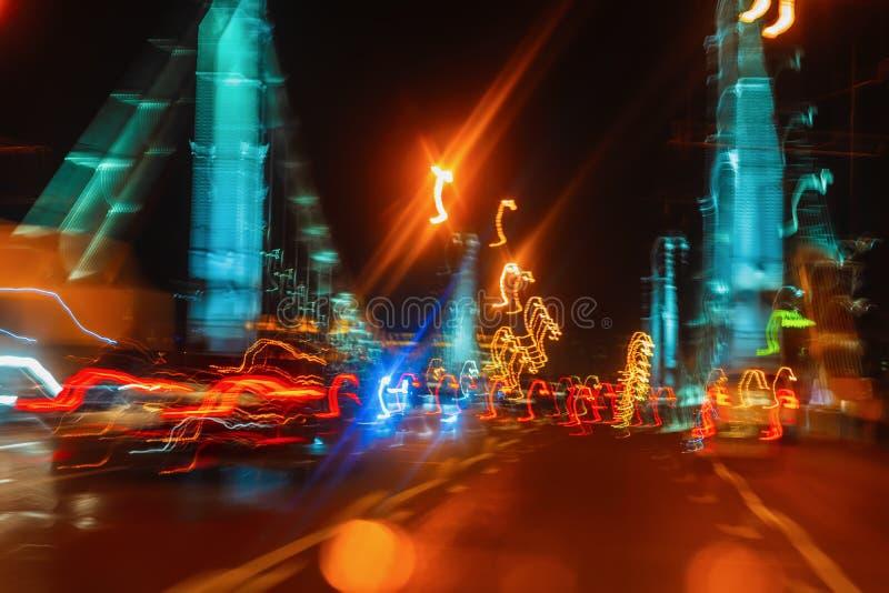 驾驶在城市桥梁在晚上,有都市街道照明的,行动迷离移动的汽车 概念的现代 免版税图库摄影