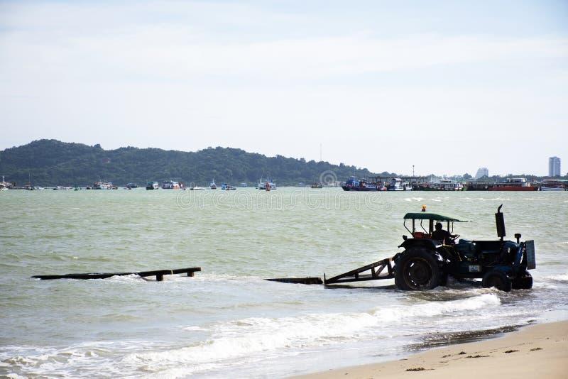 驾驶拖拉机的泰国人去保留的海和移动速度小船去存放在禁令Pae海滩在罗勇,泰国 图库摄影