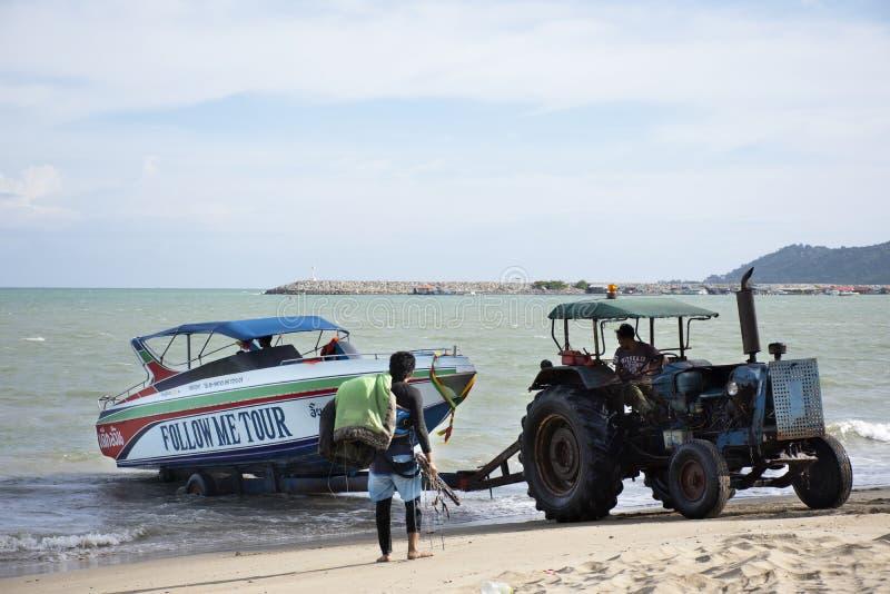 驾驶拖拉机的泰国人去保留的海和移动速度小船去存放在禁令Pae海滩在罗勇,泰国 免版税库存照片