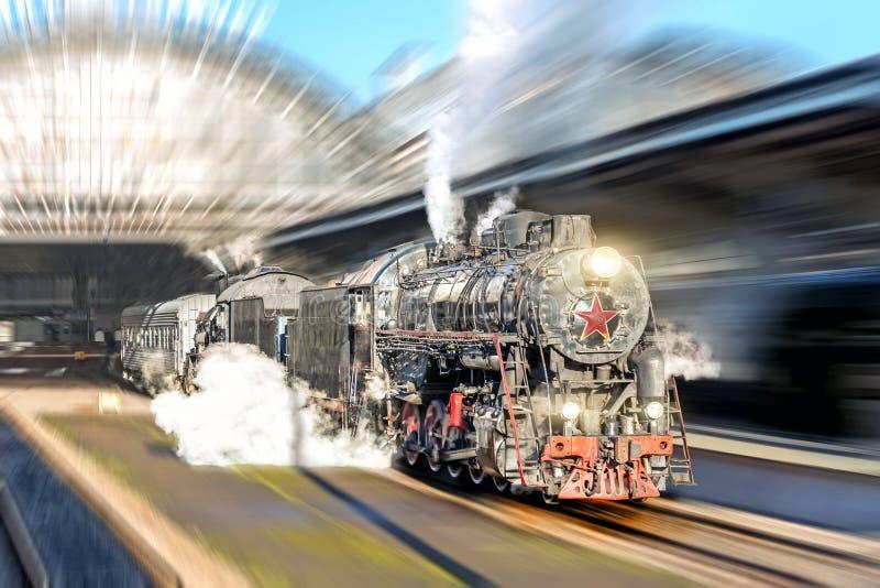 驾驶通过驻地的乘客平台的老蒸汽火车机车 免版税库存图片