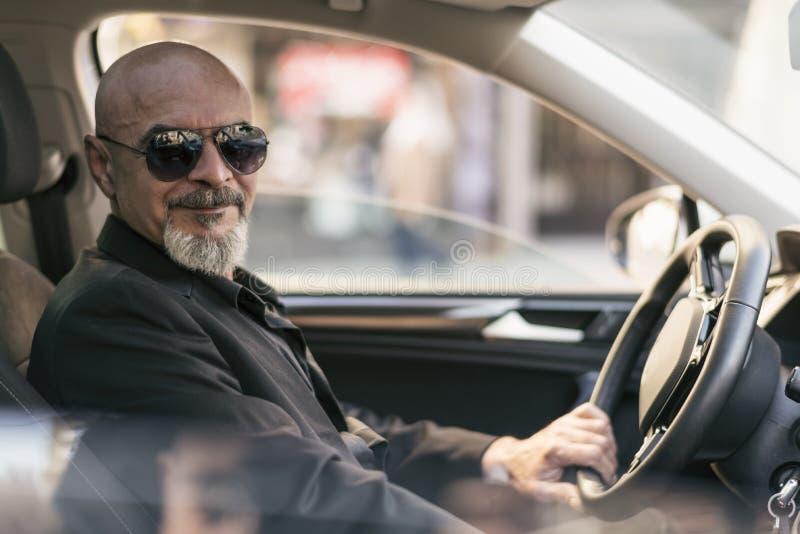驾驶suv豪华汽车的资深60s人 免版税库存图片