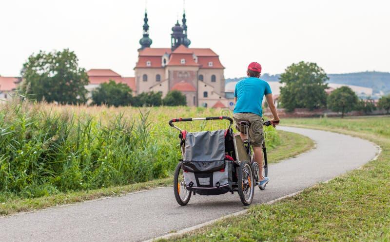 骑有孩子的父亲一辆自行车拖车的 图库摄影