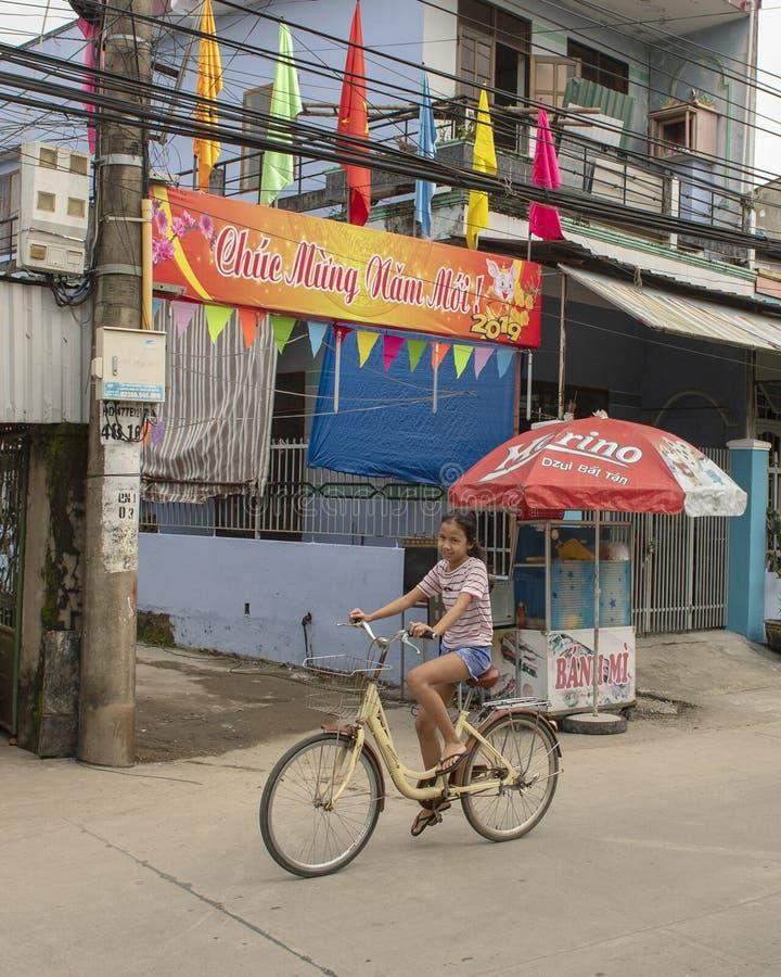 骑有2019新年快乐横幅的孩子一辆自行车在背景,Phuong Nam,越南中 库存图片
