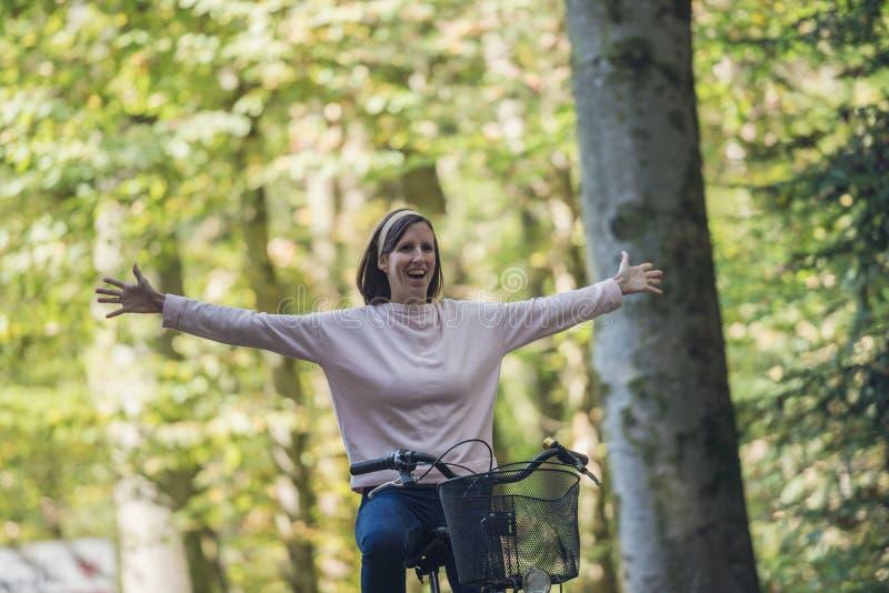 骑自行车的愉快的年轻女人通过森林 免版税库存图片