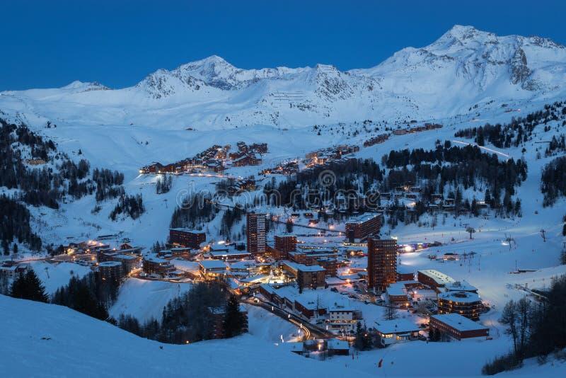 高处滑雪场看法在法国萨瓦山在微明下:皮拉涅中心、皮拉涅索莱伊和皮拉涅村庄 库存图片