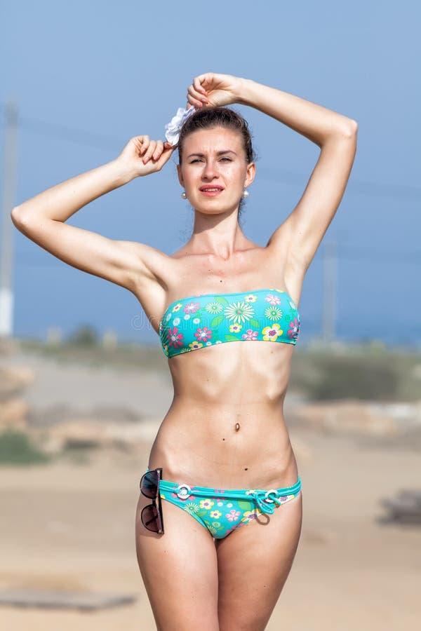 高妇女画象绿色泳装的在海滩 免版税库存图片