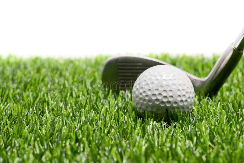 高尔夫球和高尔夫俱乐部在草在白色背景 库存照片