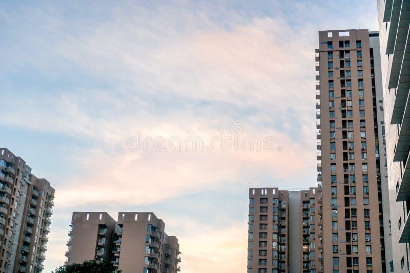 高层建筑物低角度射击在gurgaon德里的反对多云天空 免版税库存图片