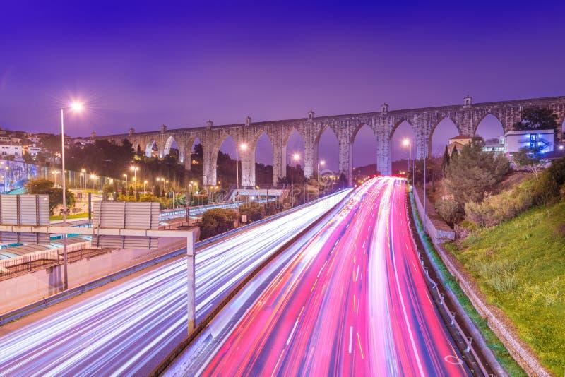 高速公路看法有汽车通行和光足迹的 阿瓜里弗渡槽Aqueduto das à  guas里弗在里斯本,葡萄牙 图库摄影