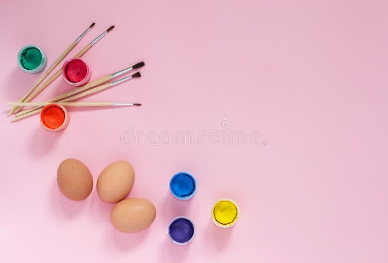 鸡鸡蛋、油漆和刷子复活节框架  绘装饰的鸡蛋的艺术过程 在桃红色的复活节构成 免版税图库摄影