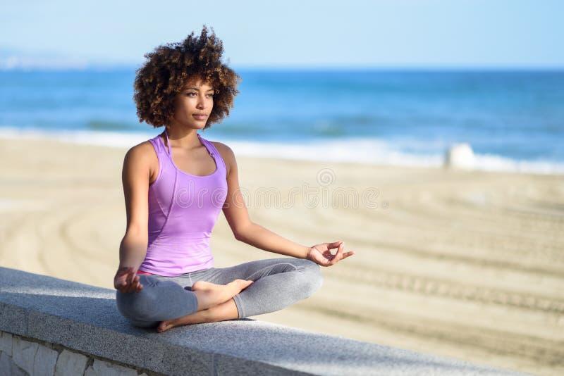 黑人妇女,非洲的发型,做在海滩的瑜伽 图库摄影