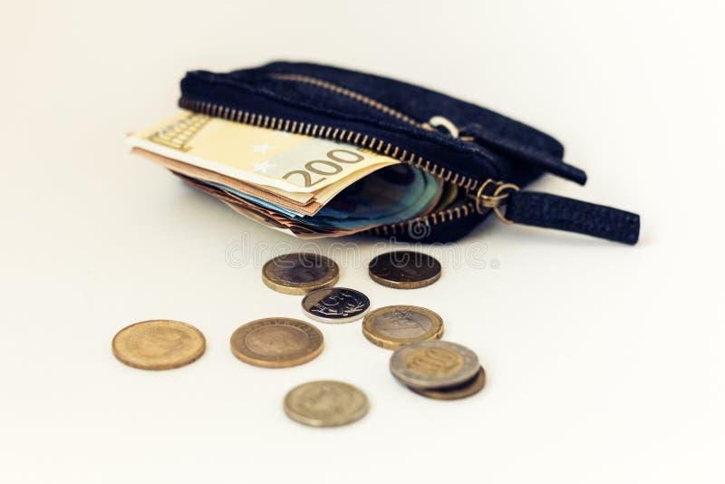 黑在与欧元和硬币的白色背景隔绝的绒面革皮革钱包 库存图片