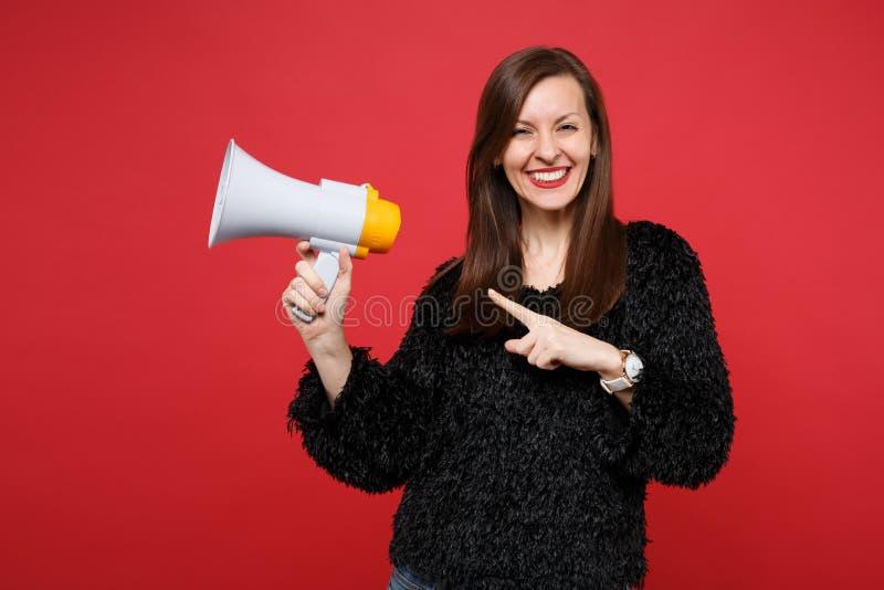 黑毛皮毛线衣的快乐的年轻女人指向食指的在旁边,拿着扩音机被隔绝在明亮的红色墙壁上 图库摄影