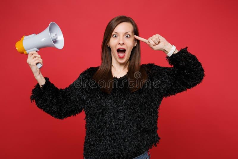 黑毛皮毛线衣的激动的年轻女人指向在头,举行扩音机的食指隔绝在明亮的红色墙壁上 免版税库存照片