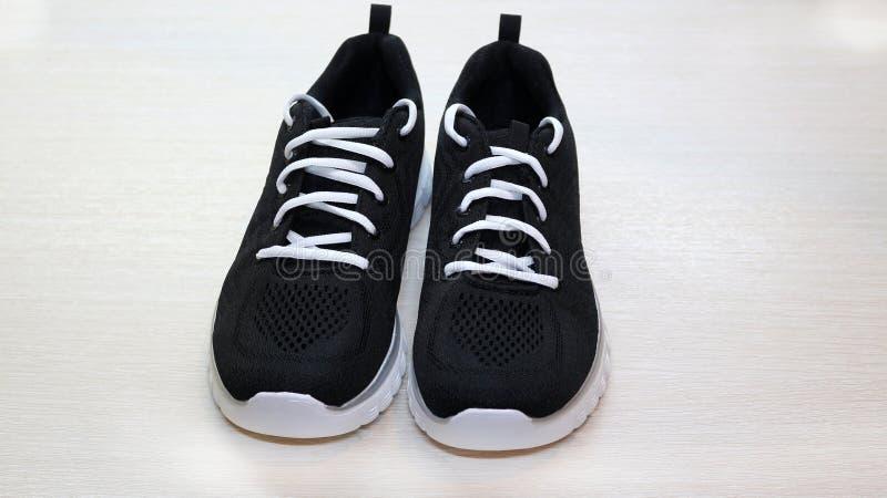 黑有白色单一和白色鞋带的体育男女皆宜的运动鞋在白色背景 库存图片
