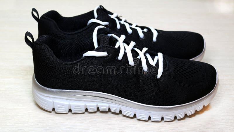黑有白色单一和白色鞋带的体育男女皆宜的运动鞋在白色背景 库存照片