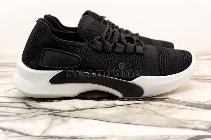 黑有白色单一和白色鞋带的体育男女皆宜的运动鞋在白色背景 免版税库存照片