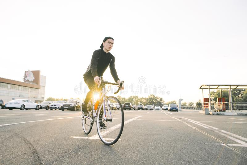 黑暗的运动服和盖帽的年轻人佩带在停车场的一辆白色自行车在阳光下 库存图片