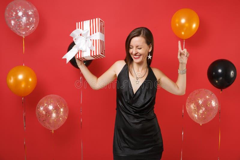 黑礼服跳舞的快乐的少女指向庆祝的举行的红色箱子的手指有礼物的,在明亮的红色 免版税库存图片