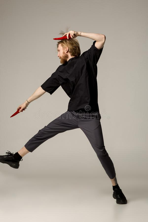 黑穿戴的一个ninja人用两个红辣椒在他的手上 免版税库存图片