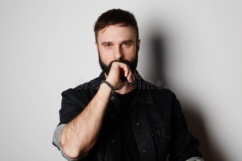 黑牛仔裤夹克的有胡子的人在空的墙壁背景 库存图片