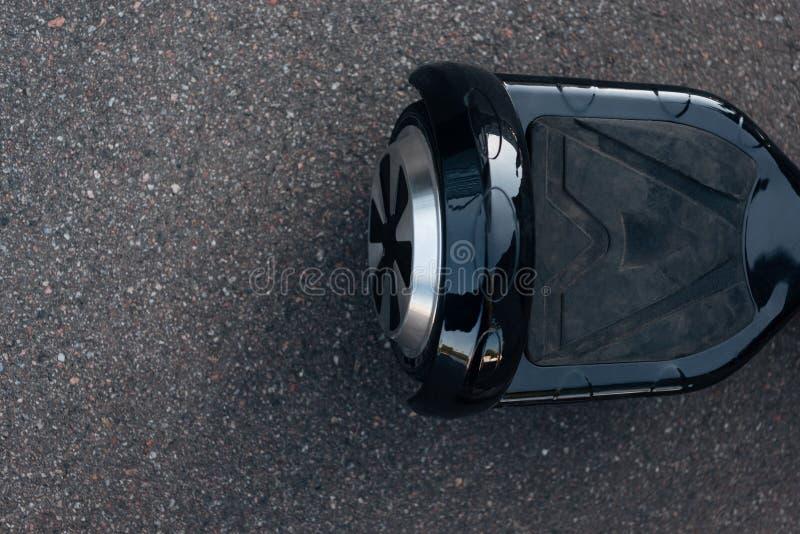 黑自平衡的滑行车顶视图在街道上的 免版税库存图片
